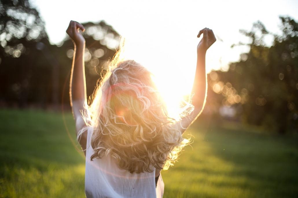 Mädchen läuft im Sonnenlicht auf einer Wiese.