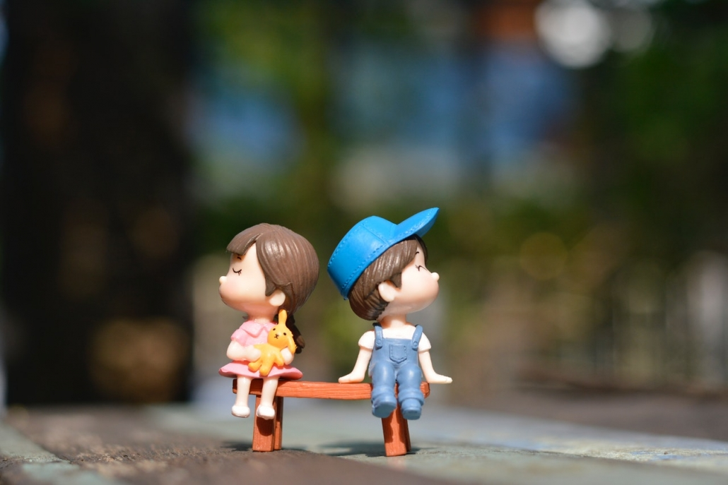 Spielzeugfiguren: Bub und Mädchen auf einer Bank. Beide typisch als Bub und Mädchen angezogen.
