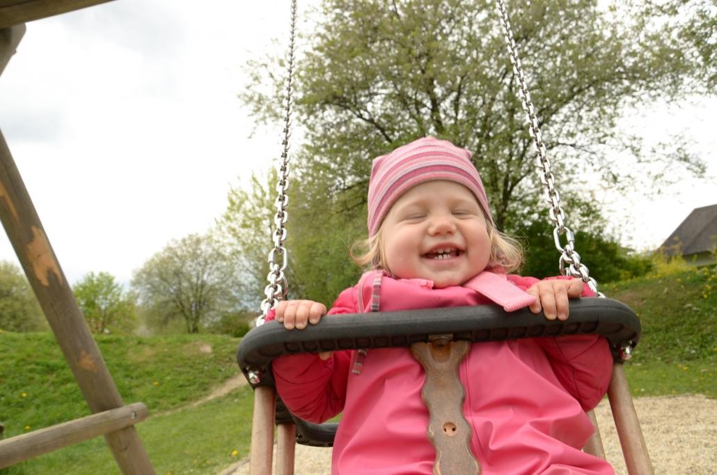 Bewegung macht den Kleinen Spaß: Kleines Kind auf Schaukel.