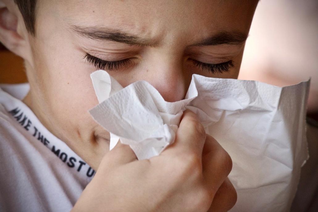 Jugendlicher mit Infekt, schneunzt in ein Taschentuch.