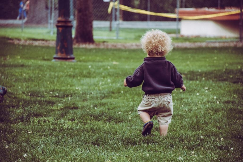Kleines Kind läuft im Gras.